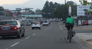 There is not enough space for a car to pass this bicyclist without using a significant portion of the adjacent lane (such that that lane would need to be free of traffic). By riding in this position, the bicyclist is creating the illusion of courtesy while exposing himself to risk of being sideswiped by a motorist who mistakenly tries to squeeze past.